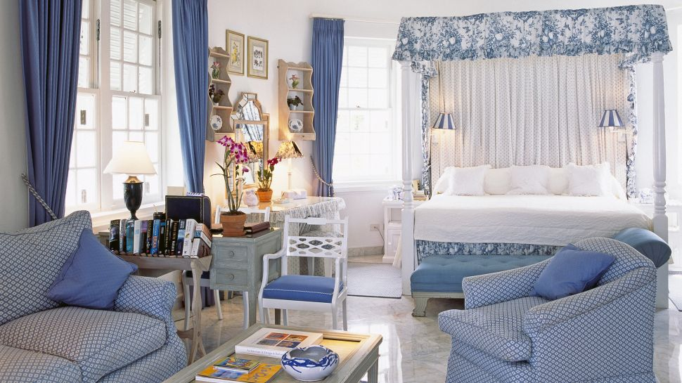 Bedroom-with-marble-tiling-floor-double-bed-blue-armchair-sofa-small-table-and-wall-lamps